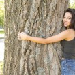 Stock Photo: Casual gorgeous brunette embracing tree looking at camera