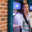 Stock Photo: Pretty happy student withdrawing cash smiling at camera
