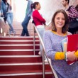 Female holding books with students on stairs in college — Stock Photo #36188865