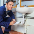 Stock Photo: Smiling plumber inspecting sink holding clipboard