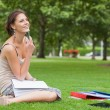 Stock Photo: Thoughtful student with books sitting at the park