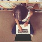Student against bookshelf using laptop on the library floor — Stock Photo #36188985