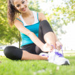 Stock Photo: Cheerful active brunette tying her shoelaces