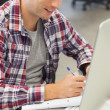 Handsome happy student using computer taking notes — Stock Photo #36189257