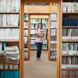 Full lenght of a female student standing in the library — Stock Photo