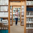 Full lenght of a female student standing in the library — Stock Photo #36189291