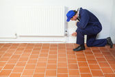 Handyman in blue boiler suit repairing a radiator — Stock Photo