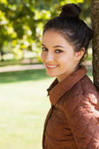 Side view of lovely woman leaning against a tree — Stock fotografie