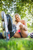 Casual smiling blonde tying shoelaces of roller blades — Stock Photo