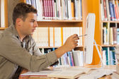 Handsome focused student pointing at computer — Stock Photo
