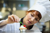 Focused head chef putting mint leaf on little cake — Stock Photo