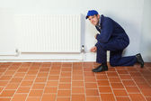 Handyman in blue boiler suit repairing a radiator smiling at cam — Stock Photo