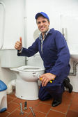 Plumber kneeling next to toilet showing thumb up — Stock Photo