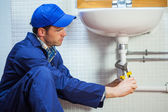 Attractive focused plumber repairing sink — Stock Photo
