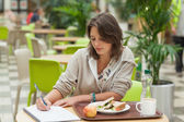 Student doing homework while having breakfast in the cafe — Stockfoto