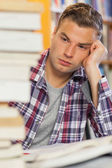 Tired handsome student studying between piles of books — Stock Photo