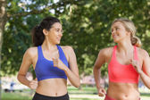 Two friendly pretty women running in a park — Stock Photo