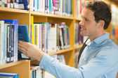 Mature student selecting book from shelf in library — Stock Photo