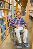 Man in wheelchair by bookshelf in library — Foto de Stock