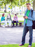 College boy text messaging with blurred students in park — Stock Photo