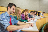 Students writing notes in a row at lecture hall — Stock Photo