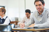 Mature students taking notes in classroom — Foto Stock