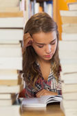 Focused pretty student studying between piles of books — Stok fotoğraf
