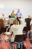 Students raising hands in the classroom — Stockfoto