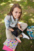 Pretty cheerful student sitting on grass using tablet — Stock Photo