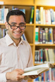 Smiling mature student with book in library — Stock Photo