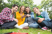 Happy college students looking at mobile phone in park — Stock Photo