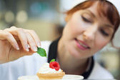 Happy head chef putting mint leaf on little cake — Stock Photo