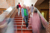 Casual handsome student standing on stairs — Stock Photo