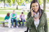 College girl using mobile phone with students in park — Stock Photo