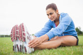 Sporty woman stretching her legs while sitting on grass — Stock Photo