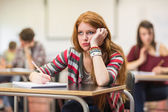 Bored female student with others writing notes in classroom — Stock Photo