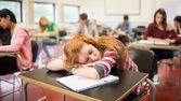 Blurred students in the classroom with one asleep girl — Stock Photo