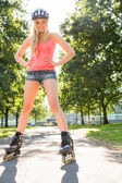 Casual cheerful blonde standing hands on hips wearing inline ska — Стоковое фото