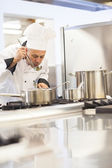 Concentrating head chef tasting food from ladle — Stock Photo