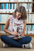Estudiante contra la estantería con tablet pc en el piso de la biblioteca — Foto de Stock