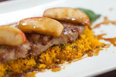 Close up of couscous with meat garnished with apple — Stock Photo