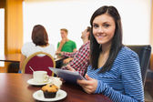 Smiling female having breakfast while using tablet PC at coffee — Stock Photo