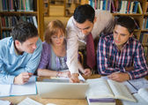 Mature students with teacher and laptop in library — Foto Stock