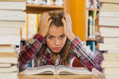 Annoyed pretty student studying between piles of books — Stock Photo