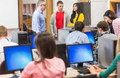 Teacher and students in the computer room — Stock Photo