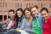 Five students sitting on the grass smiling at camera — Stock Photo