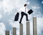 Young businessman climbing grey steps — Stock Photo