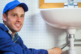 Attractive cheerful plumber repairing sink — Stock Photo