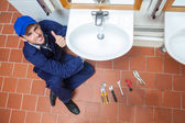 Cheerful plumber repairing sink showing thumb up — Stock Photo