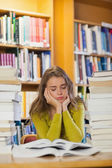 Tired student between piles of books with closed eyes — Stock Photo